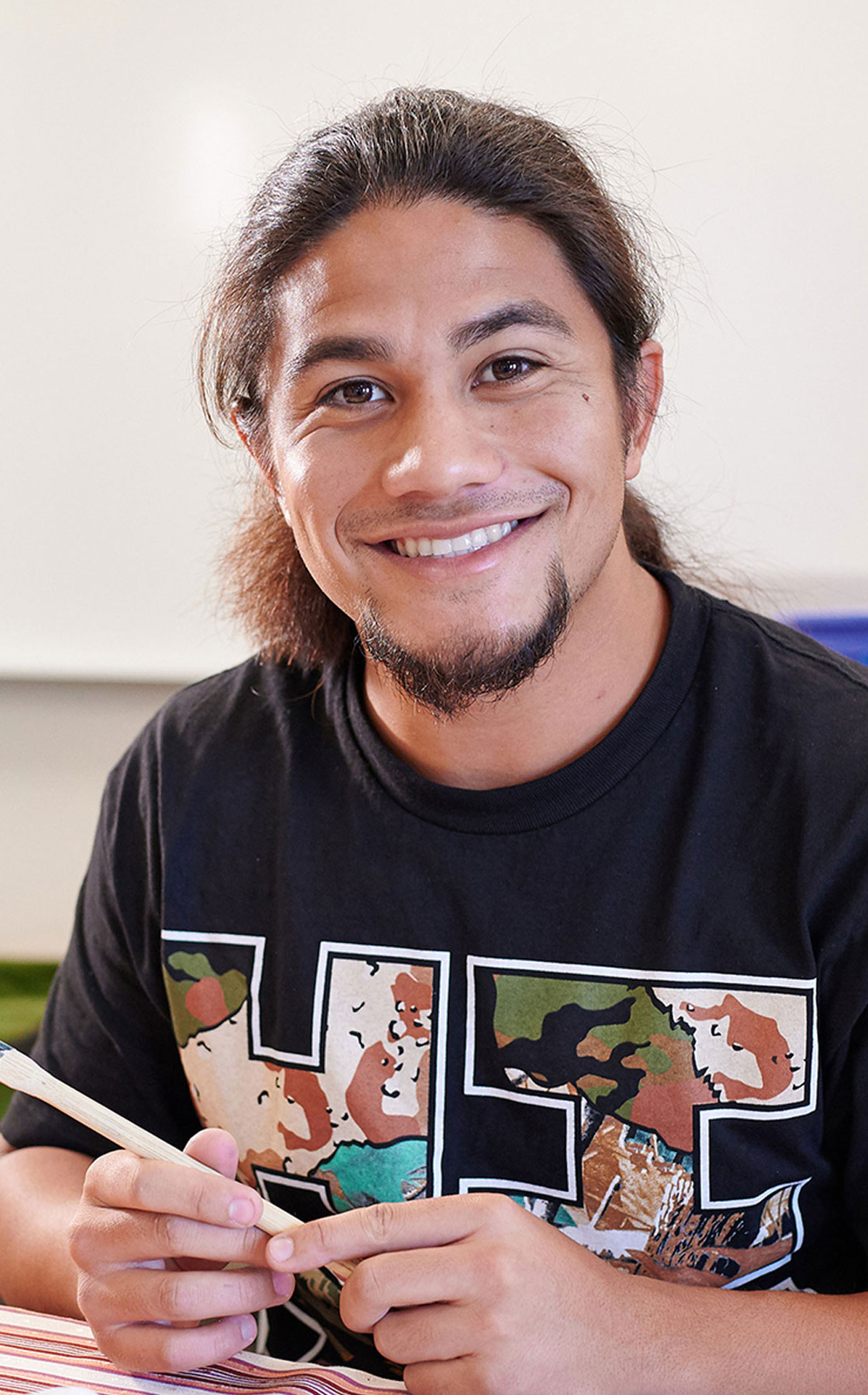 Close-up Of A Student Smiling In A Classroom With A Black T-shirt.