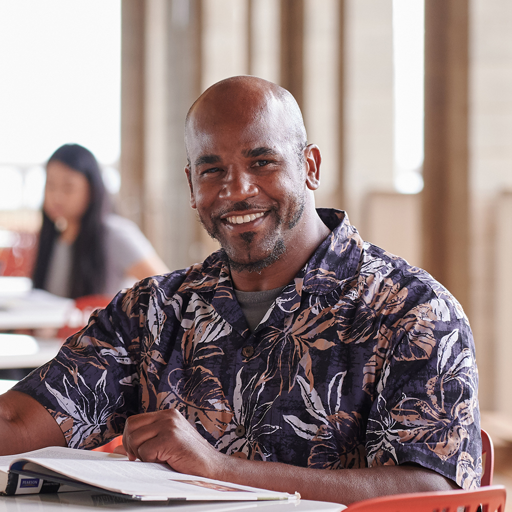 A Close-up Of A Veteran Student Sitting At A Table In The Hallway Of The Health Science Building.