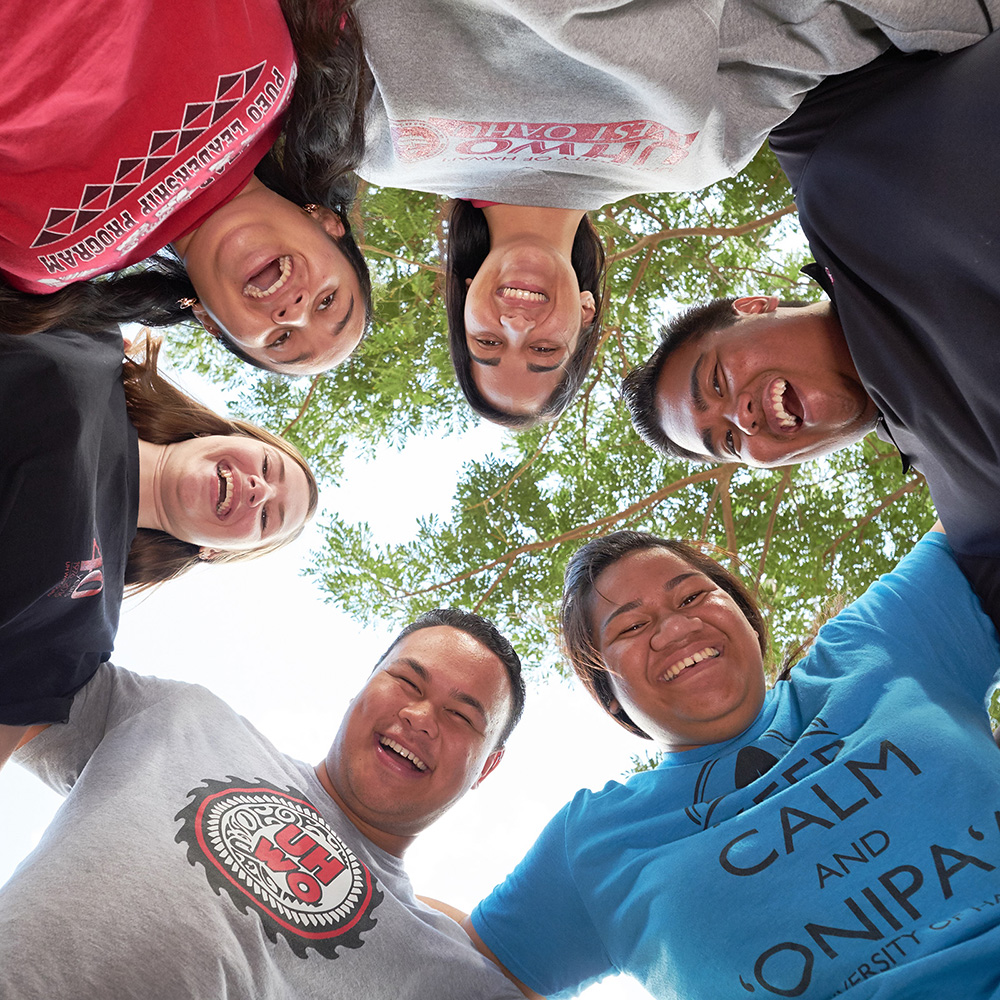 A Group Of 6 Students Looking Downward Toward The Camera That Is Facing The Sky.