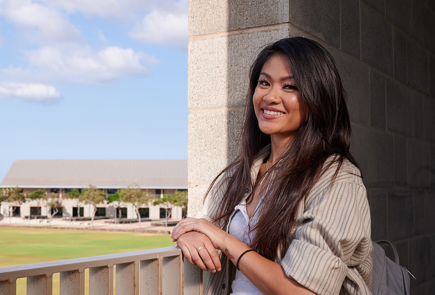 A student smiling by the railing of the second level of the Health Sciences building.