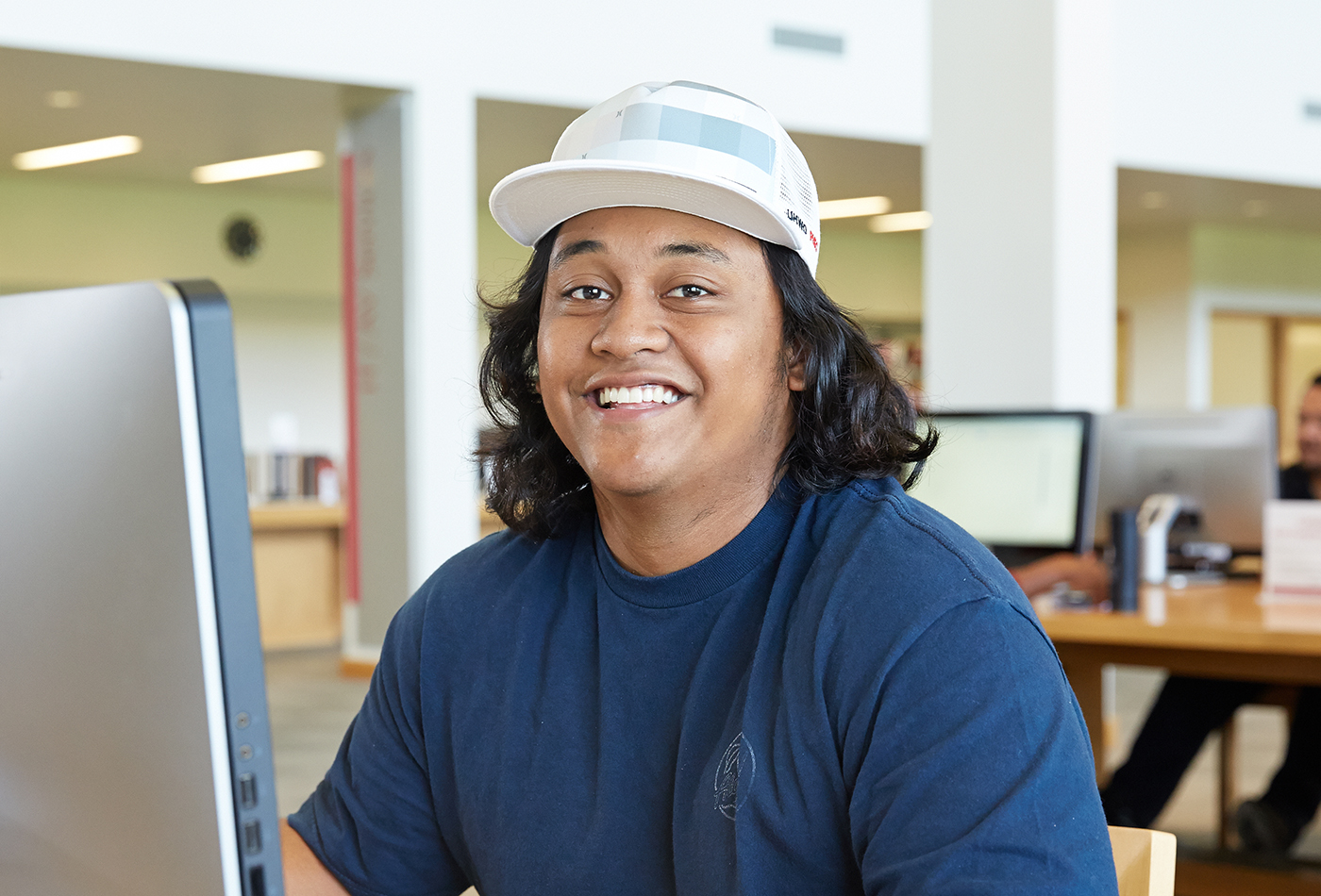 A student in a white cap smiling while sitting at a computer station in the library.