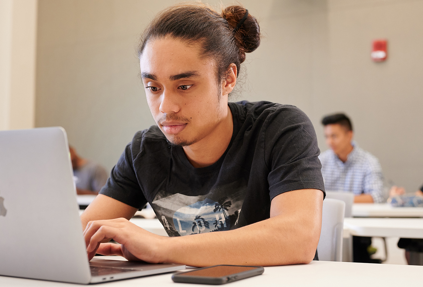 A student studying on a laptop in class.