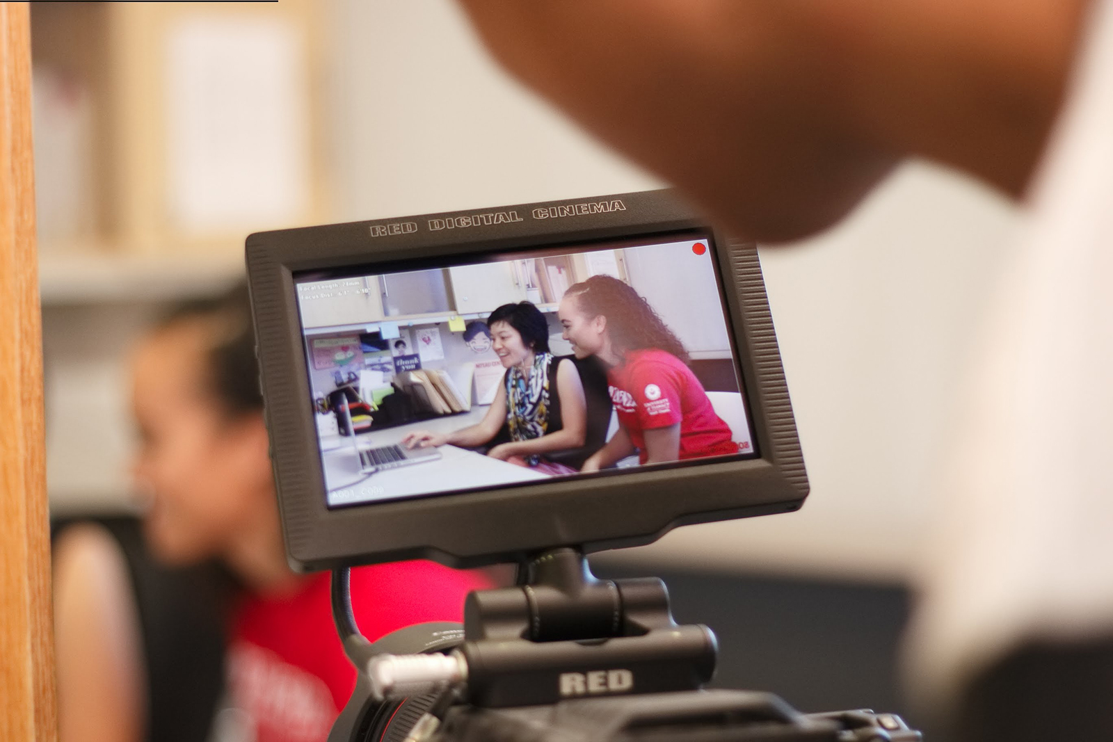 A student and a tutor seen through a camera viewfinder.