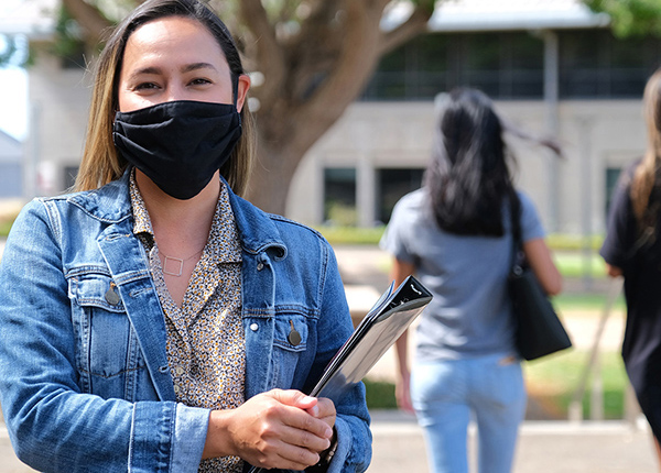 A Student Holding A Binder, While Wearing A Mask.
